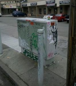 A ground mounted telephone cross box. Note the graffiti and vandalism. PHOTO COURTESY OF SENSORCITIES.COM